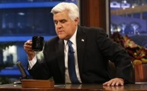 Host Jay Leno sits at his desk during a commercial break while taping the last episode of