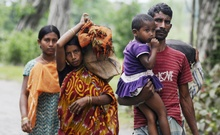 Muslims of East Bengali origin in Assam running away after their houses were burned down by suspected Bodo militants in Khagrabari village of Assam's Baksa district on May 3.