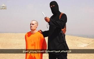 Masked IS militant speaks next to man purported to be James Foley in this still image from an undated video posted on a social media. Photo: Reuters