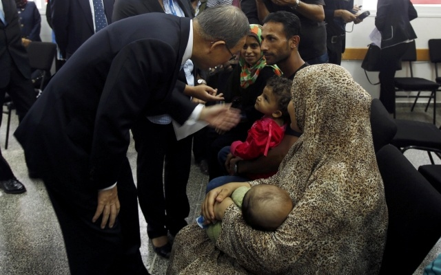 United Nations Secretary-General Ban Ki-moon (L) speaks with Palestinians, whose houses were destroyed during a seven-week Israeli offensive, as he visits a UN-run school where homeless people take refuge in Gaza City October 14, 2014. Reuters