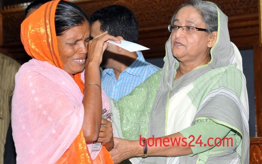 Prime Minister Sheikh Hasina hands over cheques to the family members of the workers who died in the Savar builing collapse at her office on Wednesday.