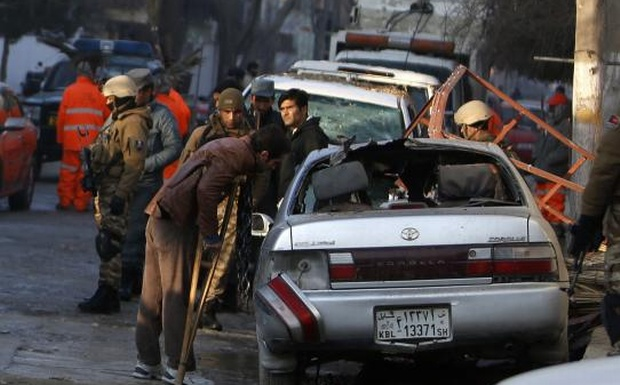 Fawad, a worker of a Lebanese restaurant who was injured during a suicide bombing attack outside the restaurant, looks at a damaged vehicle near the restaurant in Kabul January 18, 2014.  Credit: Reuters