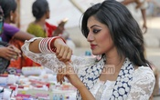 A girl buys Churi in front of Dhaka University's Institute of Fine Arts at Shahbagh in Dhaka on Friday ahead of the celebrations of the Pahela Boishakh, the first day of Bengali New Year. Photo: nayan kumar/ bdnews24.com