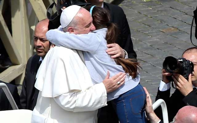 Pope Francis embraces a girl during the Palm Sunday mass at Saint Peter's Square at the Vatican April 13, 2014. REUTERS