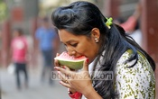 A girl eating watermelon from a street shop in Dhaka's Gulisthan, for a respite from the scorching summer heat, on Tuesday afternoon. Photo: nayan kumar/ bdnews24.com