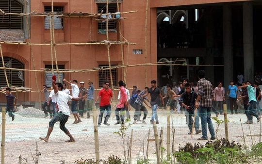 Barisal University students clash with RAB and police after blocking the Barisal-Patuakhali Highway in protest against a fellow student being pushed out of a bus. Photo: bdnews24.com