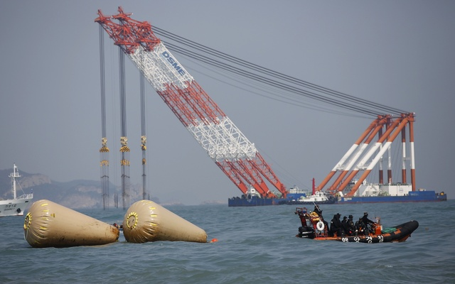 Rescue workers operate near floats as a giant offshore crane, which will take part in the rescue operation, is seen in the background where the capsized passenger ship Sewol sank, during the rescue operation in the sea off Jindo April 20, 2014. REUTERS
