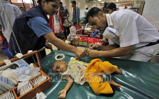 A brother sets a saline bag for a diarrhoea patient at ICDDR,B in Dhaka where hundreds of such patients have been admitted. Photo: nayan kumar/ bdnews24.com