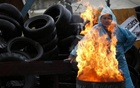 A pro-Russia protester warms himself by the fire on a barricade outside a regional government building in Donetsk, in eastern Ukraine April 20, 2014. Credit: Reuters