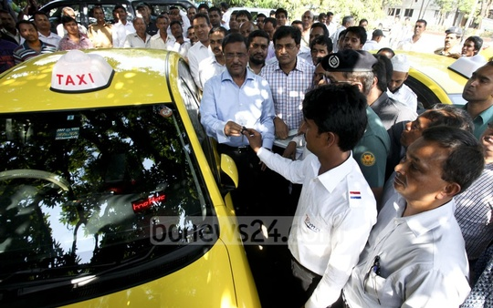 Communications Minister Obaidul Quader hands the key of taxi cab to a driver after launching the new taxi service run by Toma Construction and Company Ltd, a private organisation in Dhaka on Tuesday. Photo: asaduzzaman pramanik/ bdnews24.com