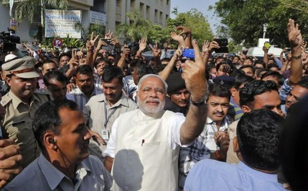 Hindu nationalist Narendra Modi (C) shows his ink-marked finger to his supporters after casting his vote at a polling station during the seventh phase of India's general election in Ahmedabad April 30, 2014. Credit: Reuters