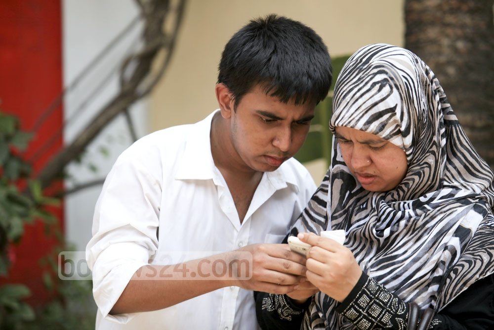 A candidate and his mother surf internet on mobile to see result at Motijheel Ideal School and College on Saturday. Photo: asaduzzaman pramanik/ bdnews24.com