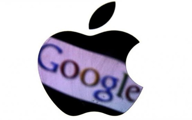 A Google trademark is reflected in Apple logo in this photo illustration taken in Berlin, August 31, 2012. Credit: Reuters