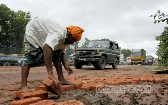 Workers mending the Dhaka-Mymensingh highway with bricks as a quick fix at Gazipur's Rajenrdapur on Monday to cope with the heavy traffic ahead of Eid. Photo: tanvir ahammed/ bdnews24.com