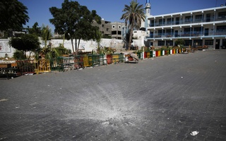 A crater marks the centre of a courtyard at a United Nations-run school sheltering Palestinians displaced by an Israeli ground offensive, that police said was hit by an Israeli shell, in Beit Hanoun in the northern Gaza Strip July 24, 2014.