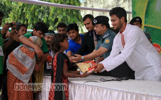 Cricketer Shakib Al Hasan and Dhaka Metropolitan Police Commissioner Benazir Ahmed distribute clothes among the poor at Kamalapur Railway Station ahead of Eid. The initiative was sponsored by FM Radio Dhaka and Pran. Photo: asif mahmud ove/ bdnews24.com