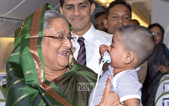 Prime Minister Sheikh Hasina holds a child in her flight back home from London on Wednesday. Photo: bdnews24.com