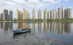 A man rows a boat on a river in front of new properties in Taiyuan, Shanxi province, July 24, 2014. Credit: Reuters