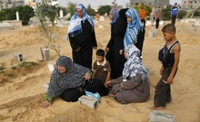 A Palestinian woman (L) mourns next to the grave of her son, who medics said was killed during the Israeli offensive, on the Muslim holiday of Eid al-Fitr at a cemetery in Beit Lahiyah in the northern Gaza Strip July 28, 2014.