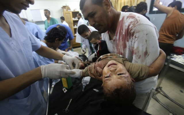 A Palestinian man carries his son, whom medics said was wounded in an Israeli air strike, as he receives treatment at a hospital in Khan Younis in the southern Gaza Strip July 30, 2014. Reuters