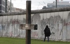 A woman walks along the former Berlin Wall border fortification at the memorial site in Bernauer Strasse in Berlin in this November 9, 2013 file picture. Credit: Reuters