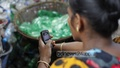 A plastic factory worker checks her phone while working in the factory located beside a Buriganga tributary in Dhaka. Photo: nayan kumar/ bdnews24.com