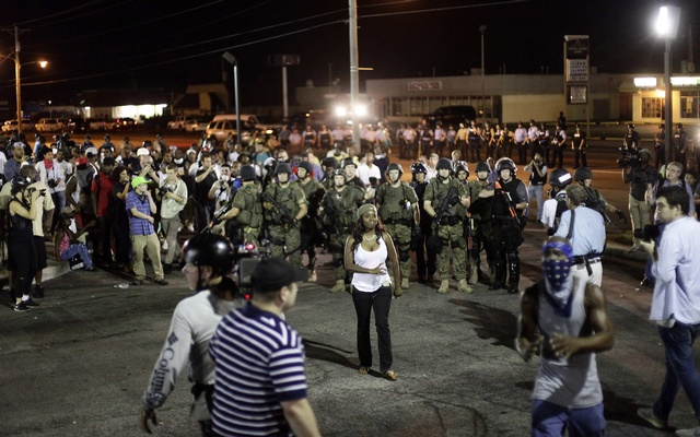 Demonstrators protesting against the shooting of Michael Brown are surrounded by police in riot gear in Ferguson, Missouri August 19, 2014. REUTERS