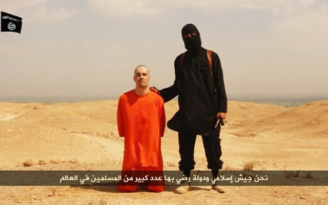 A masked Islamic State militant holding a knife speaks next to man purported to be US journalist James Foley at an unknown location in this still image from an undated video posted on a social media website. Islamic State insurgents released the video on August 19, 2014. REUTERS