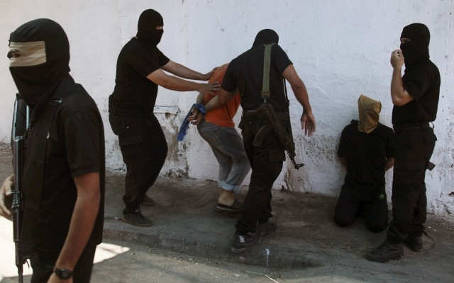 Hamas militants surround Palestinians suspected of collaborating with Israel before executing them in Gaza City August 22, 2014. REUTERS
