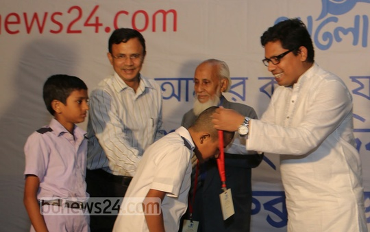 State Minister for ICT Junaid Ahmed Palak hands out souvenirs to young journalists selected in the Hello child journalism festival at Cox's Bazar Ocean Paradise Hotel. Photo: mustafiz mamun/ bdnews24.com