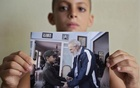 Eight-year-old Marlon Mendez, who claims to be an admirer of Cuba's former president Fidel Castro, holds a picture of him and Castro, in San Antonio de los Banos, outside Havana City August 23, 2014. Reuters
