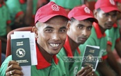 Cheerful Bangladeshi workers display their passports as they wait to board a flight to Malaysia at the Shahjalal International Airport on Wednesday. Photo: asaduzzaman pramanik/ bdnews24.com