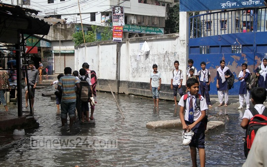 Students of Kuratoli High School have been wading through dirty water to go to class for more than a month because of waste that has blocked the sewage lines. Photo: asif mahmud ove/ bdnews24.com