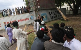 Anti-government protesters pull a rope to remove a container barricade during the Revolution March in Islamabad September 2, 2014. Credit: Reuters