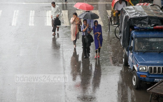 Life goes on in the busy capital amid a sudden autumn shower on Tuesday. Photo: asif mahmud ove/ bdnews24.com