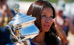 Li Na of China swats at a fly as she poses with the Daphne Akhurst Memorial Cup she won in the women's singles final match at the Australian Open 2014 tennis tournament, during a photo call at Brighton Beach in Melbourne, January 26, 2014. Reuters