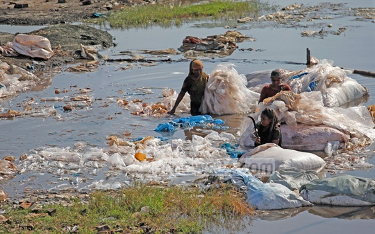 Workers of a Hazaribagh tannery wash polythene in waist-deep toxic water of the factory. Photo: nayan kumar/ bdnews24.com