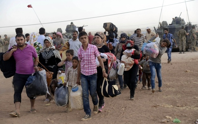 Syrian Kurds walk with their belongings after crossing into Turkey at the Turkish-Syrian border, near the southeastern town of Suruc in Sanliurfa province, September 20, 2014. REUTERS