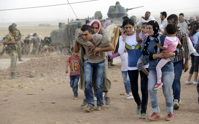Syrian Kurds walk after crossing into Turkey at the Turkish-Syrian border, near the southeastern town of Suruc in Sanliurfa province, September 20, 2014. REUTERS