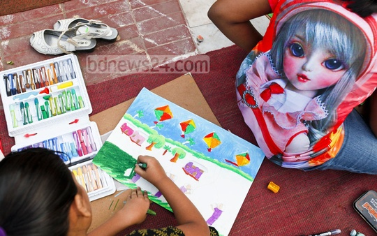 A child draws a picture at Central Shaheed Minar on Monday at an art competition on the occasion of World Children's Day and Child Rights Week. Photo: asaduzzaman pramanik/ bdnews24.com