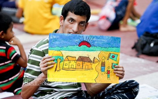 A child with autism holds up his artwork after an art competition on the first day of the children's cultural festival at the Central Shaheed Minar on Monday. Photo: asaduzzaman pramanik/ bdnews24.com
