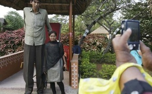 A visitor poses with Polipaka Gattaiah, who stands at seven-and-a-half feet and claims to be the tallest man in India, at the arts and crafts centre in Hyderabad in this Dec 6, 2011, file photo. Credit: Reuters