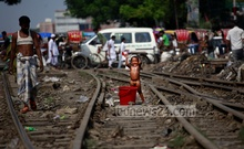 A child washes herself on railway tracks. Photo taken from Dhaka's Karwan Bazar area on Thursday. Photo: nayan kumar/ bdnews24.com