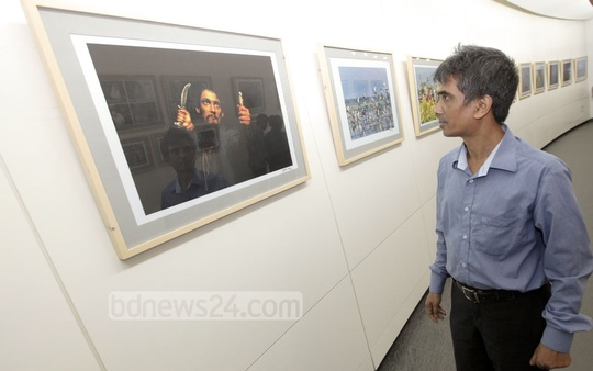 A visitor at the photo exhibition marking bdnews24.com's eighth anniversary at Bay's Galleria in Gulshan on Friday. Photo: bdnews24.com