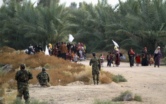 Iraqi families surrender to Shia fighters and Iraqi Army after they took control of Jurf al-Sakhar from Islamist State militants October 27, 2014. The families, who were in militant-held areas, surrendered to the army to be transported to safe areas and escape clashes between militants and Iraqi security forces. Picture taken October 27, 2014. Reuters