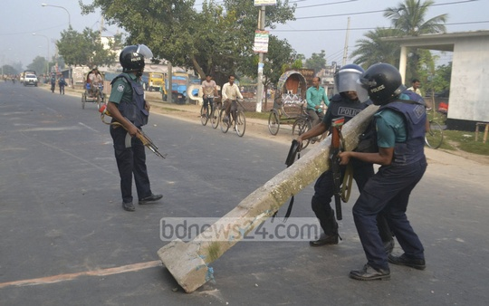 Police are removing posts laid across road by strike supporters at Rajshahi's Dingidoba area on Thursday. Photo: Gulbar Ali Juwel/ bdnews24.com