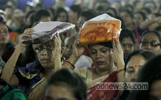 Buddhist devotees carry 'Chibor', or robe, on their head at Dhaka's Merul Badda Vihara during 'Kathin Chibor Dan' festival on Friday. Photo: tanvir ahammed/ bdnews24.com