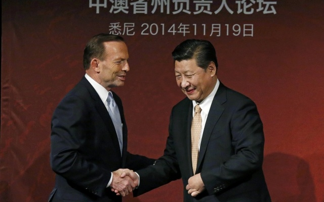China's President Xi Jinping (R) and Australia's Prime Minister Tony Abbott shake hands on stage after they both addressed the Australia-China state and provincial leaders forum in Sydney November 19, 2014. REUTERS