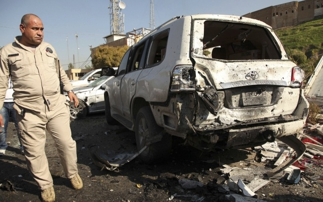 A member of the Kurdish security forces inspects the site of a car bomb attack in Arbil, the capital of Iraq's Kurdistan region ,November 19, 2014. A suicide bomber driving a car packed with explosives blew himself up in the capital of Iraq's Kurdistan region on Wednesday, killing at least five people in the first big attack there in more than a year. The Arbil mayor told Reuters the assailant had detonated himself as he tried to enter the governor's compound, which is protected by blast walls, in the centre of Arbil. REUTERS/