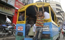 A child calls passengers hanging from a small stand at the back of a vehicle at Gulistan. Photo: asif mahmud ove/ bdnews24.com